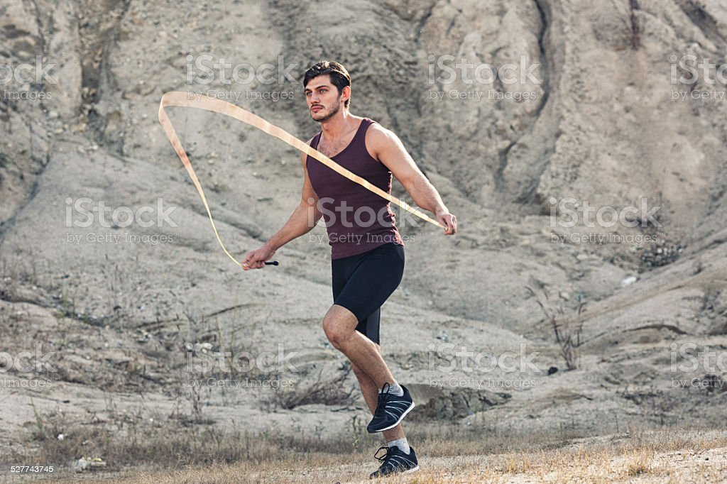 sporty man jumping rope outdoors stock photo