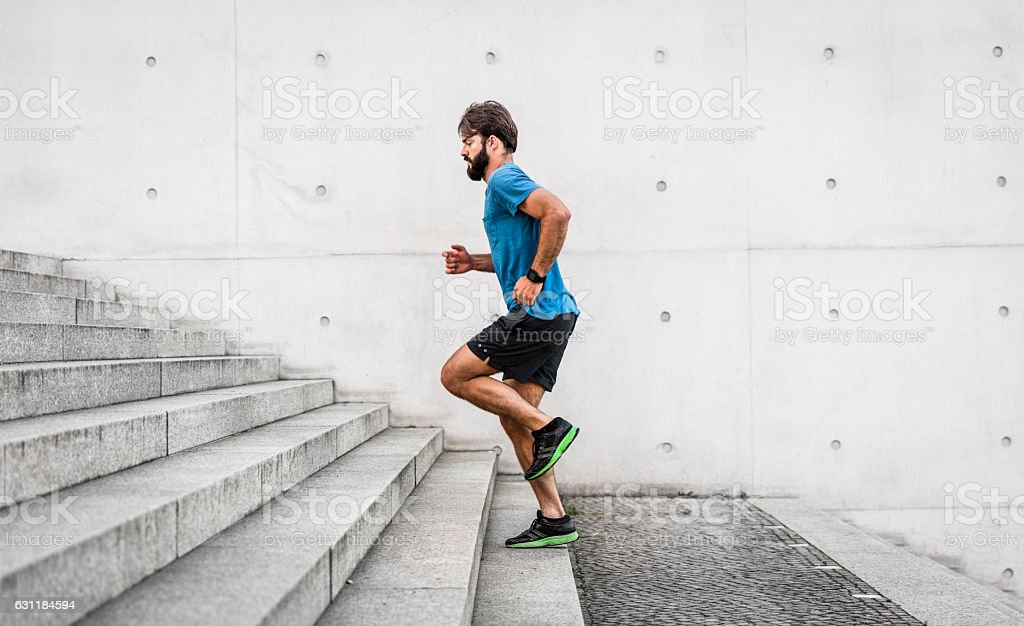 sporty man running up steps in urban setting stock photo