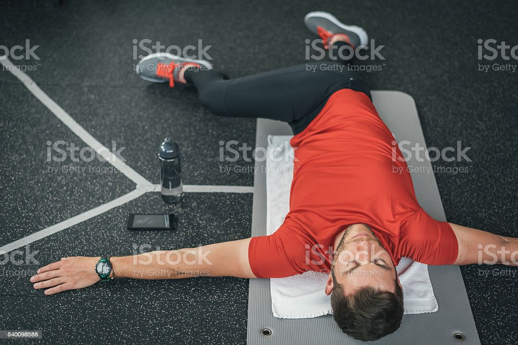 Sporty man stretching back before gym workout indoor on mat stock photo