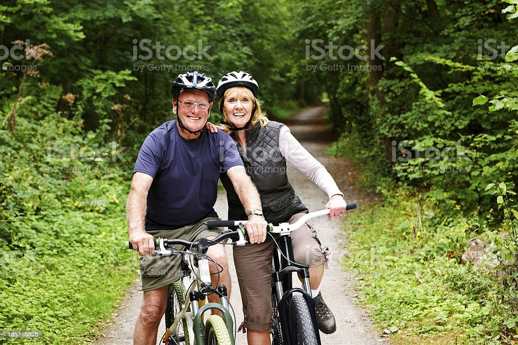 Sporty mature couple with bicycle in countryside royalty-free stock photo