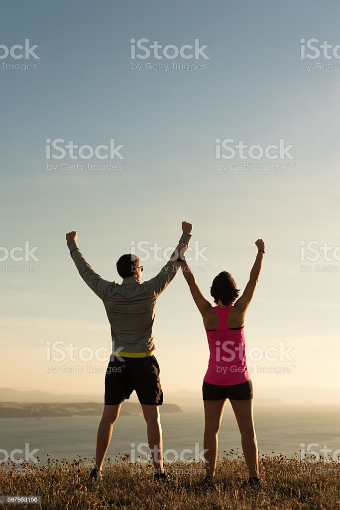 Sporty runner couple rising arms in victory sign outdoor stock photo