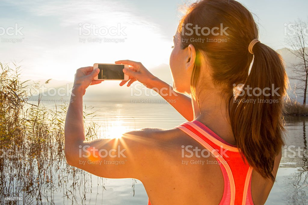 Sporty woman by the lake photographing sunset with mobile phone stock photo