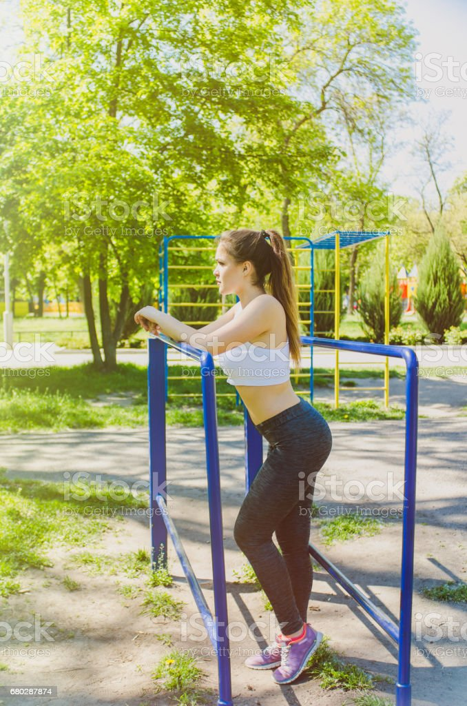 Sporty woman does the exercises outdoor stock photo