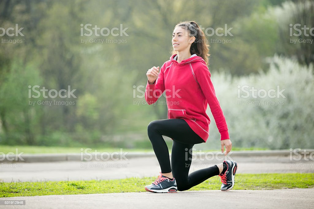 Sporty woman doing lunge exercises before running stock photo
