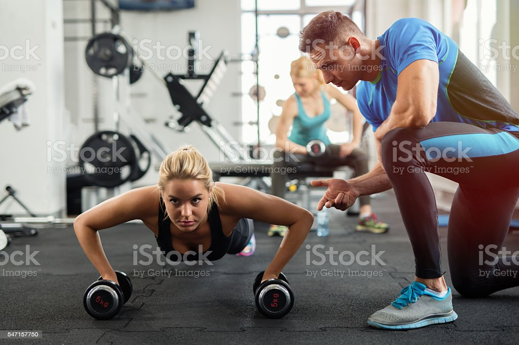Sporty woman doing push-ups under supervision of  personal trainer. stock photo