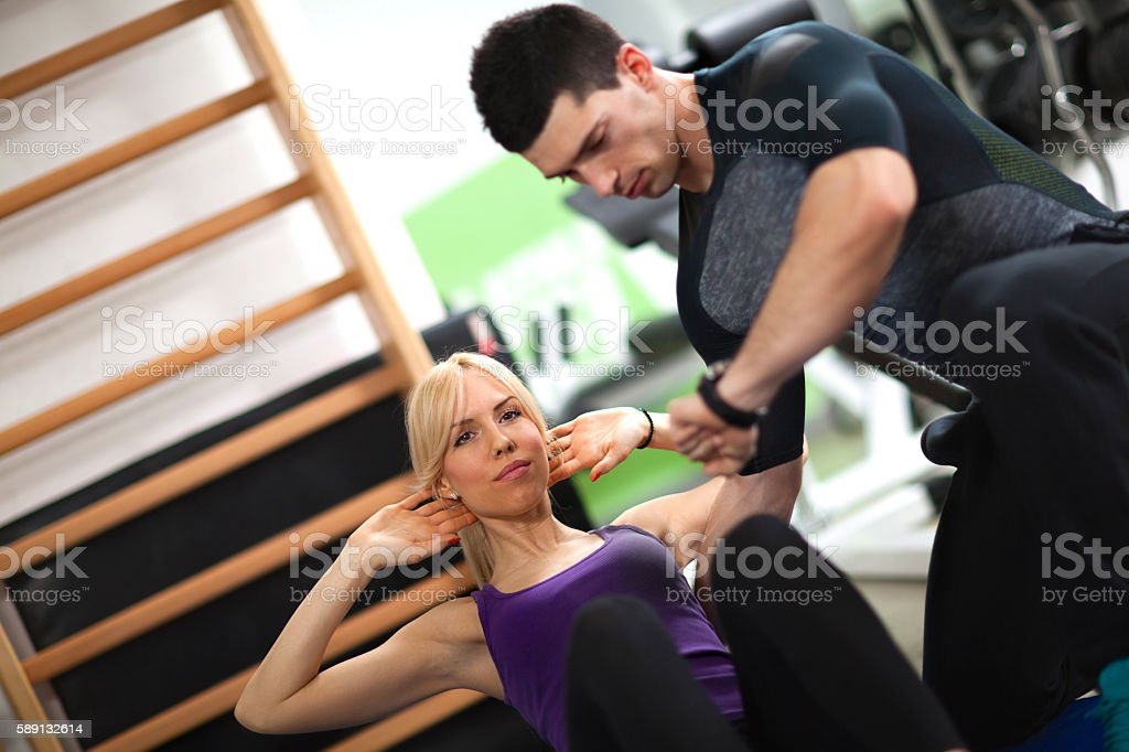 Sporty woman doing sit-ups under supervision of personal trainer. stock photo