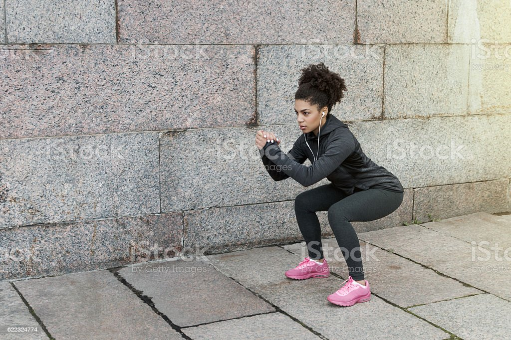 Sporty woman doing warm up squat, stretching near a wall stock photo