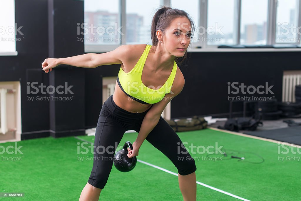 sporty woman doing work-out swinging kettlebell in gym stock photo