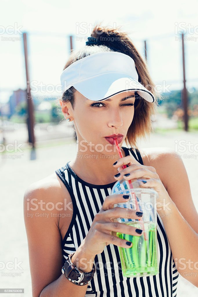 Sporty woman drinking water against the sportsground stock photo