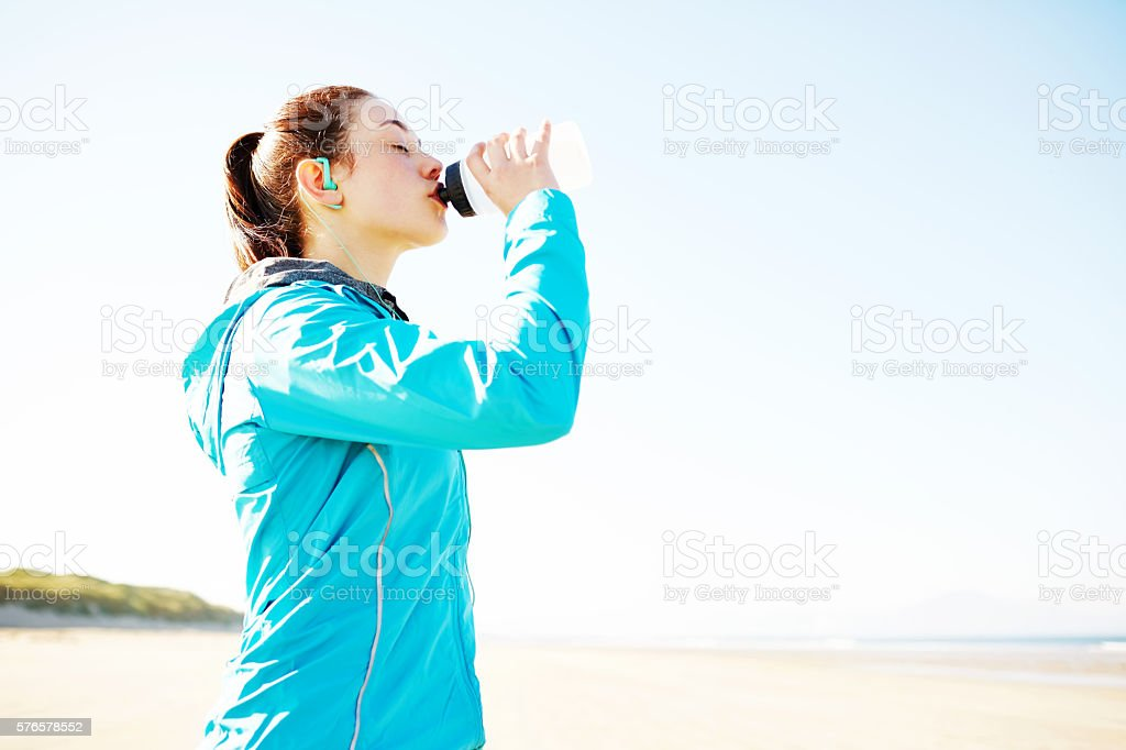 Sporty woman drinking water on beach after exhausting workout stock photo
