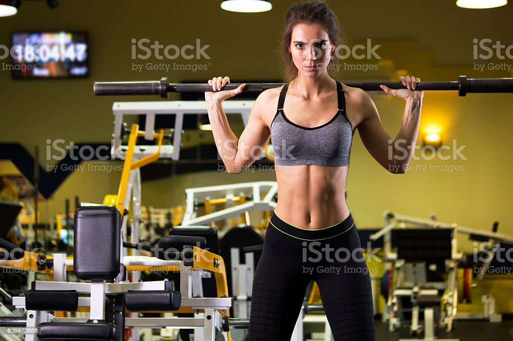 Sporty woman exercising with barbell in gym. stock photo