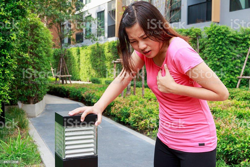 Sporty woman having heart attack - Angina Pectoris, Myocardial I stock photo