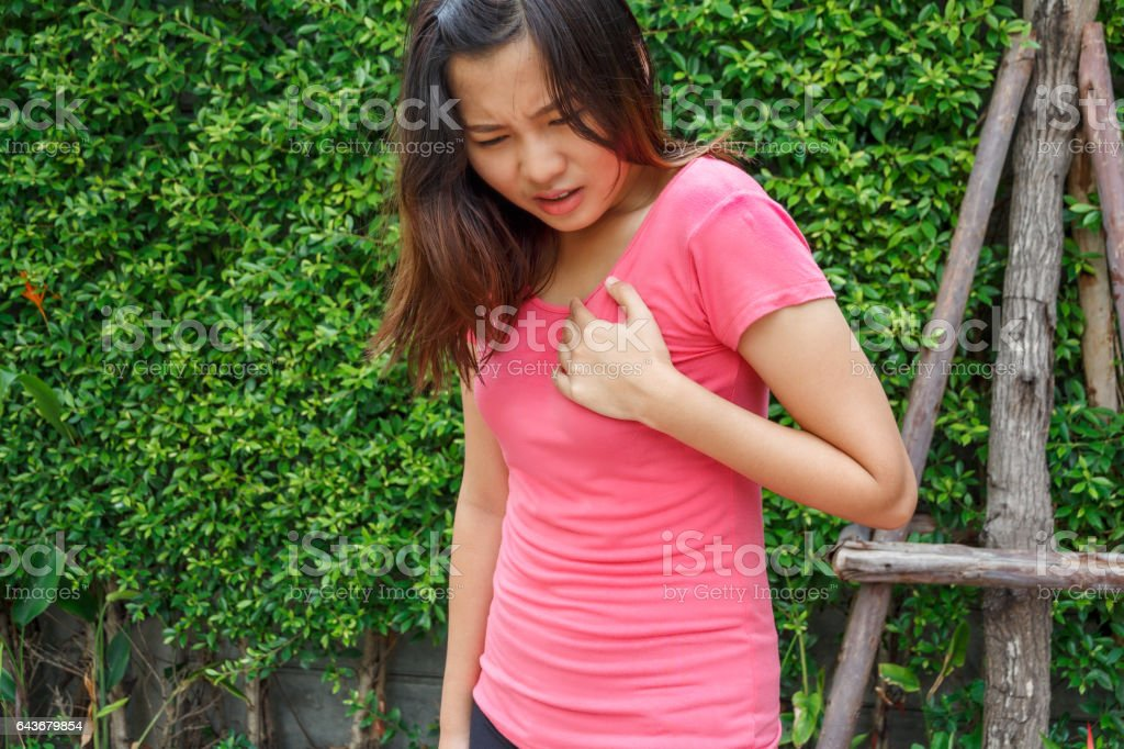 Sporty woman having heart attack - Angina Pectoris, Myocardial Infarction. stock photo