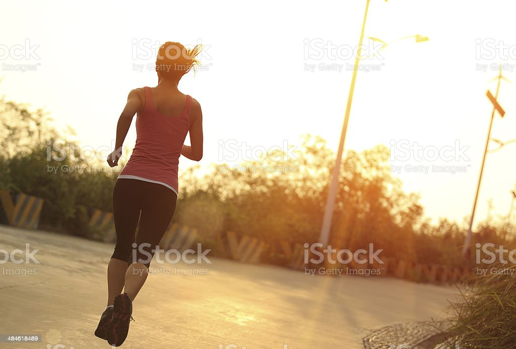 sporty woman morning exercise running on mountain driveway under sunrise stock photo