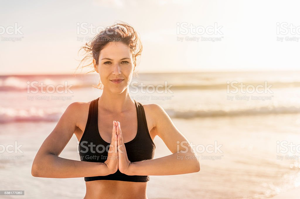Sporty woman practicing yoga at beach stock photo