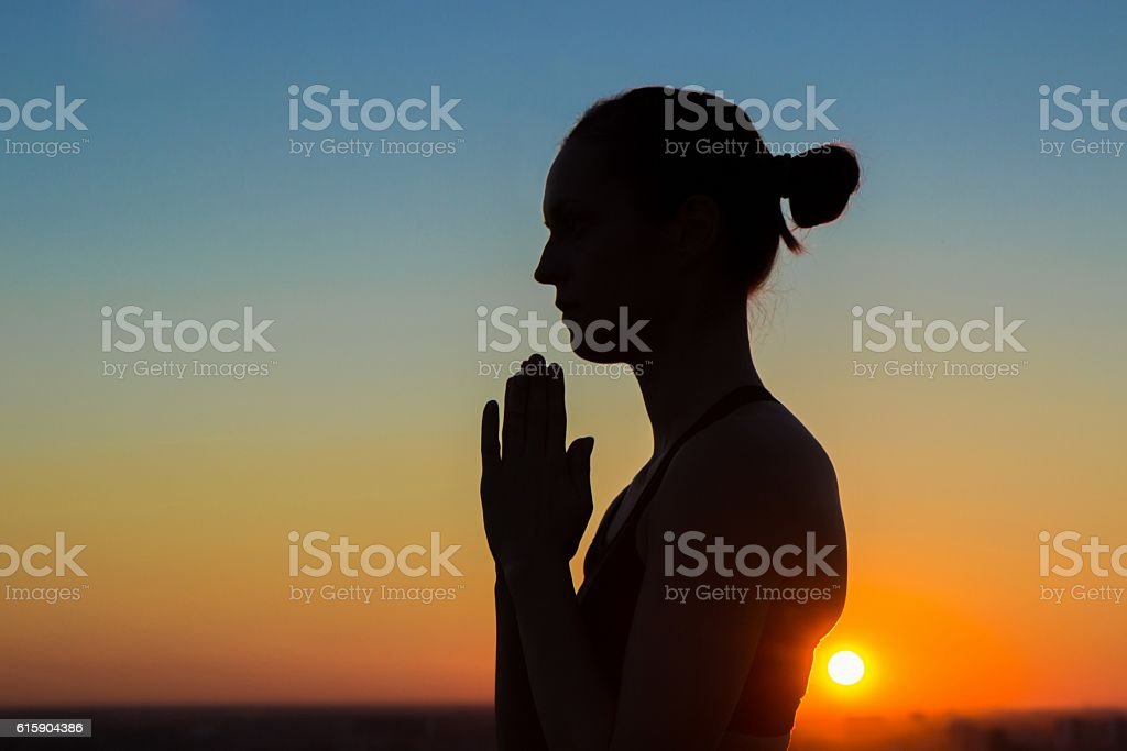 Sporty woman practicing yoga at sunset, making hand greeting namaste stock photo
