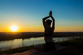 Sporty woman practicing yoga at sunset - sun salutation