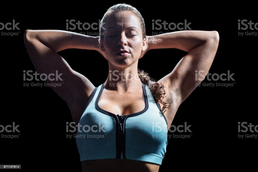 Sporty woman relaxing with hands behind head stock photo
