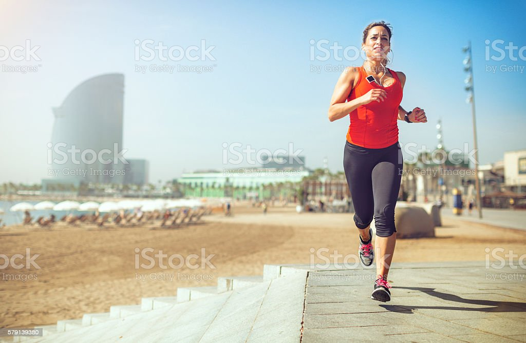 Sporty woman running and training by the beach stock photo