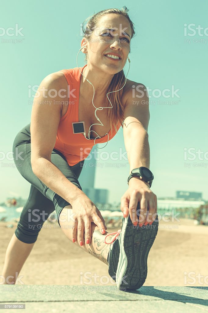 Sporty woman stretching after running stock photo