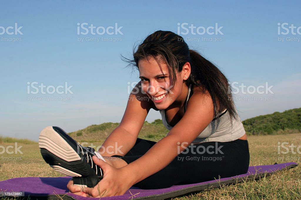 Sporty woman stretching leg on purple mat in open air royalty-free stock photo