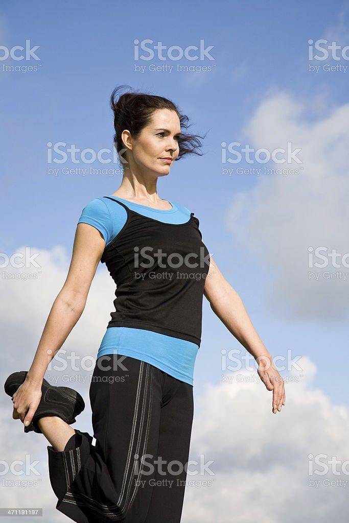 Sporty woman stretching outdoors stock photo