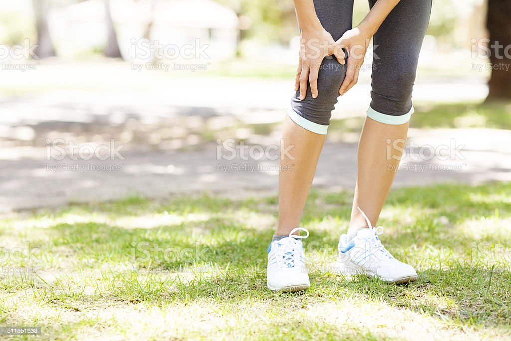 Sporty Woman Suffering From Knee Pain stock photo