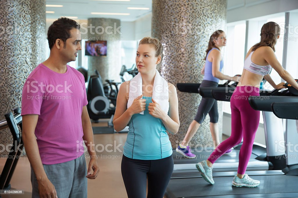 Sporty Woman Talking to Male Trainer in Gym stock photo