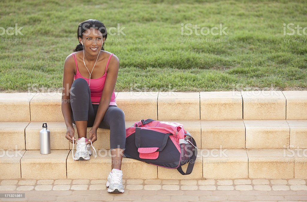 Sporty woman tying her shoelace. stock photo