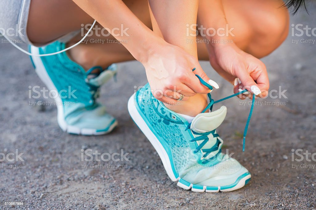 Sporty woman tying running shoe laces before jogging stock photo