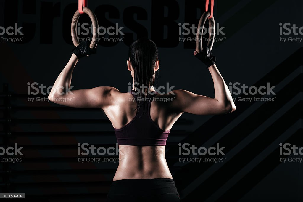 Sporty woman using gymnastic rings stock photo