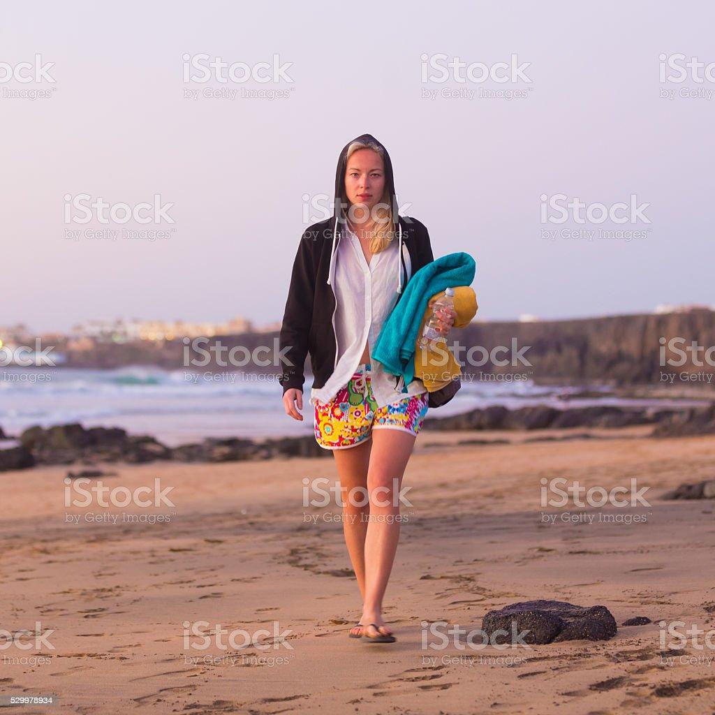 Sporty woman walking on sandy beach in sunset. stock photo