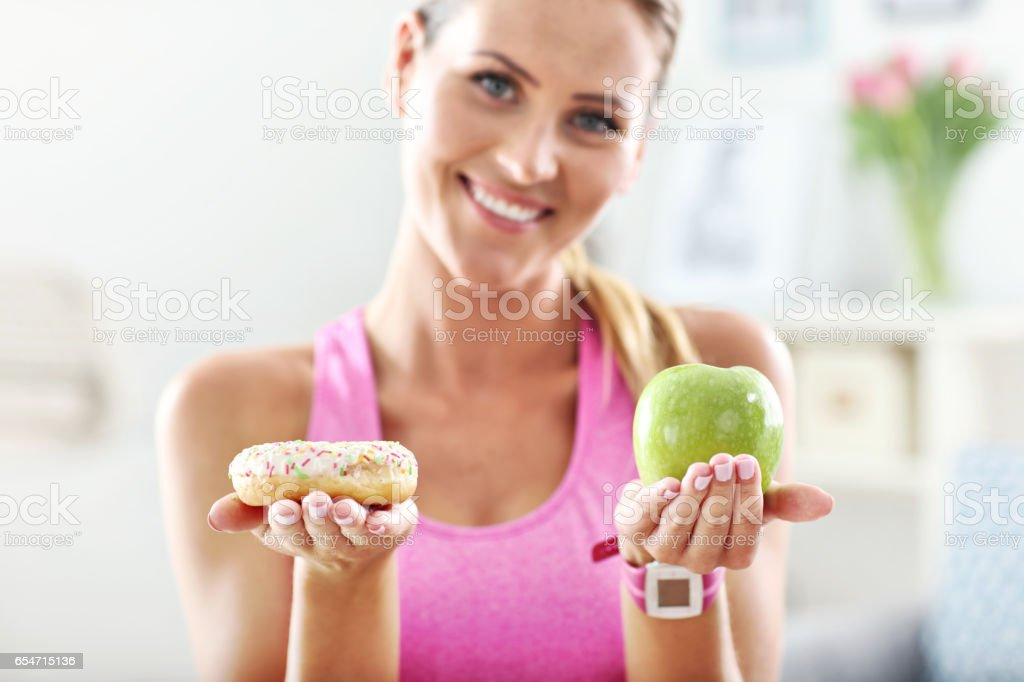 Sporty woman with apple and donut after workout stock photo