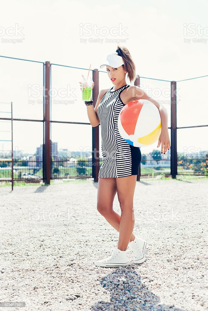 Sporty woman with color ball drinking water against the sportsground stock photo