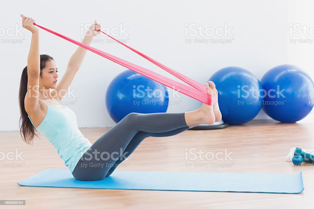 Sporty woman with exercise band in fitness studio stock photo