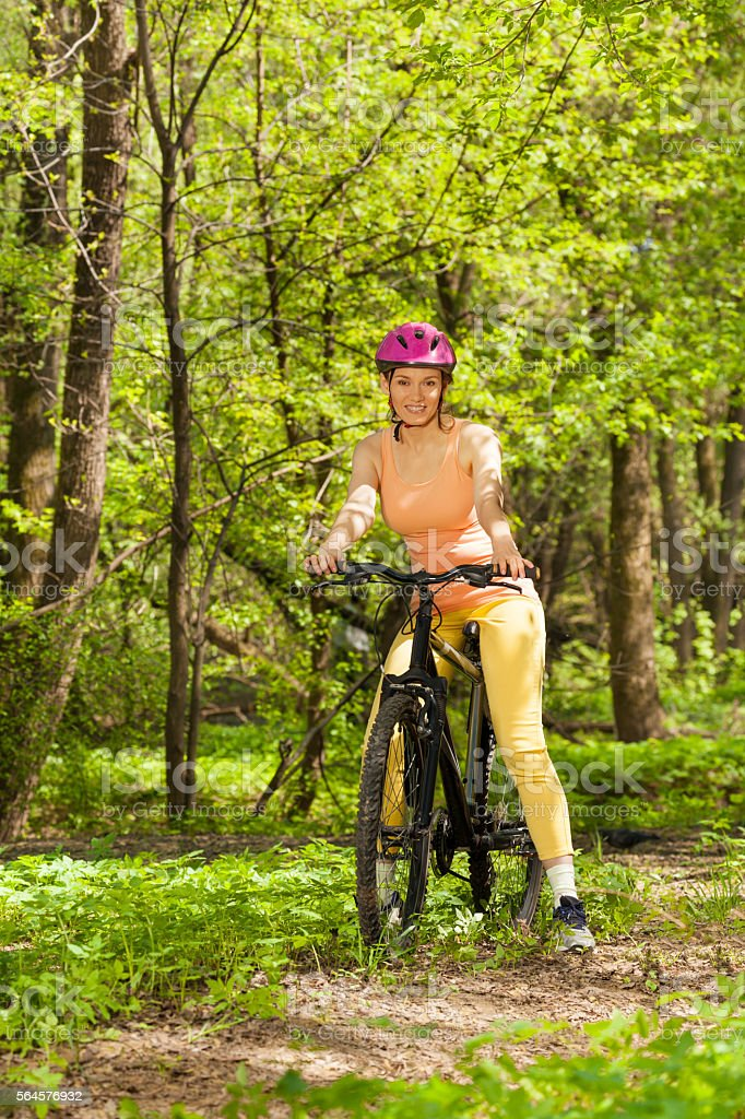 Sporty woman with mountain bike on woodland trail stock photo