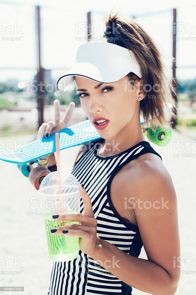 Sporty woman with skateboard drinking water against the sportsground stock photo