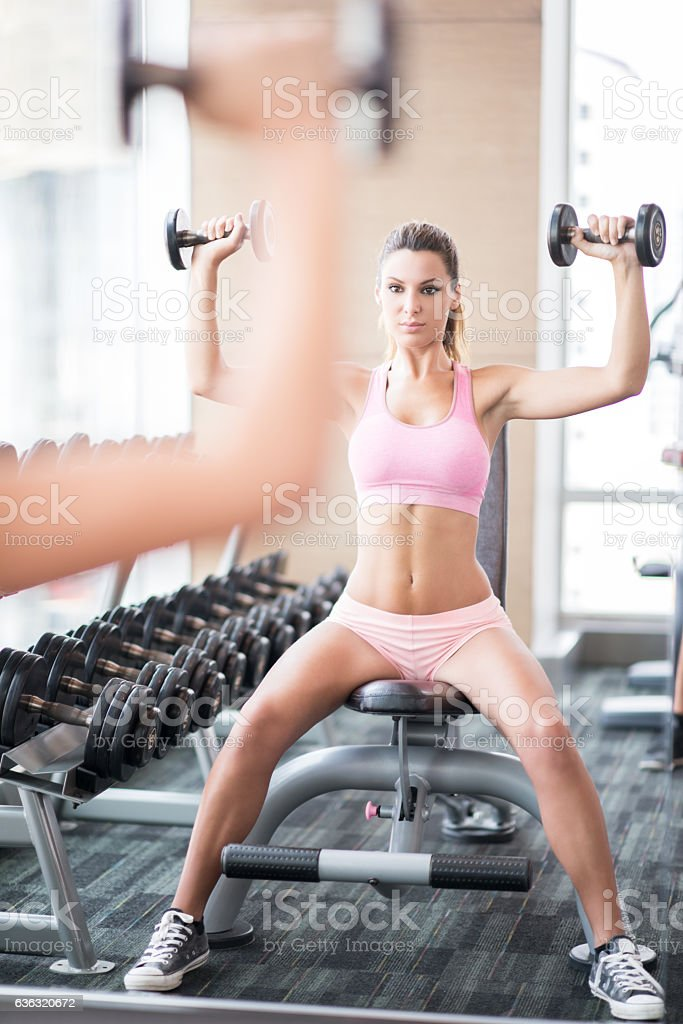 Sporty Woman working out with Dumbbells stock photo