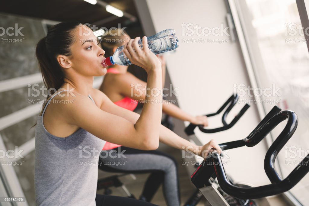 Sporty women cycling in gym during fitness class stock photo