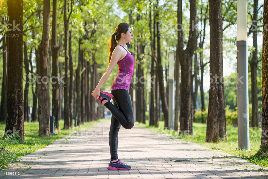 Sporty young asian woman stretching after jogging in the  forest stock photo