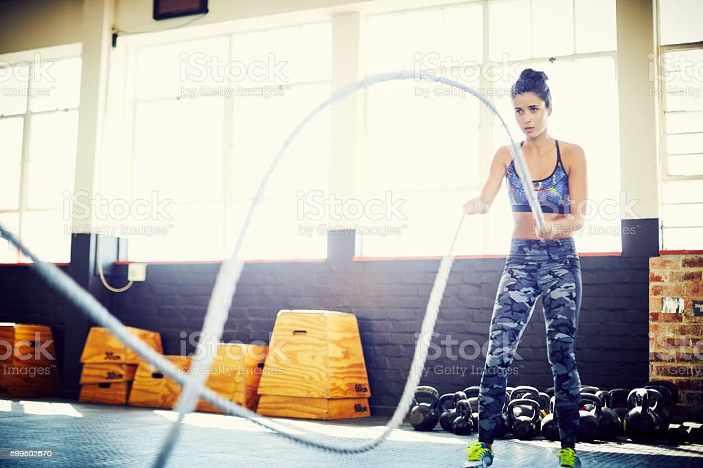 Sporty young female doing battling rope exercise at gym stock photo