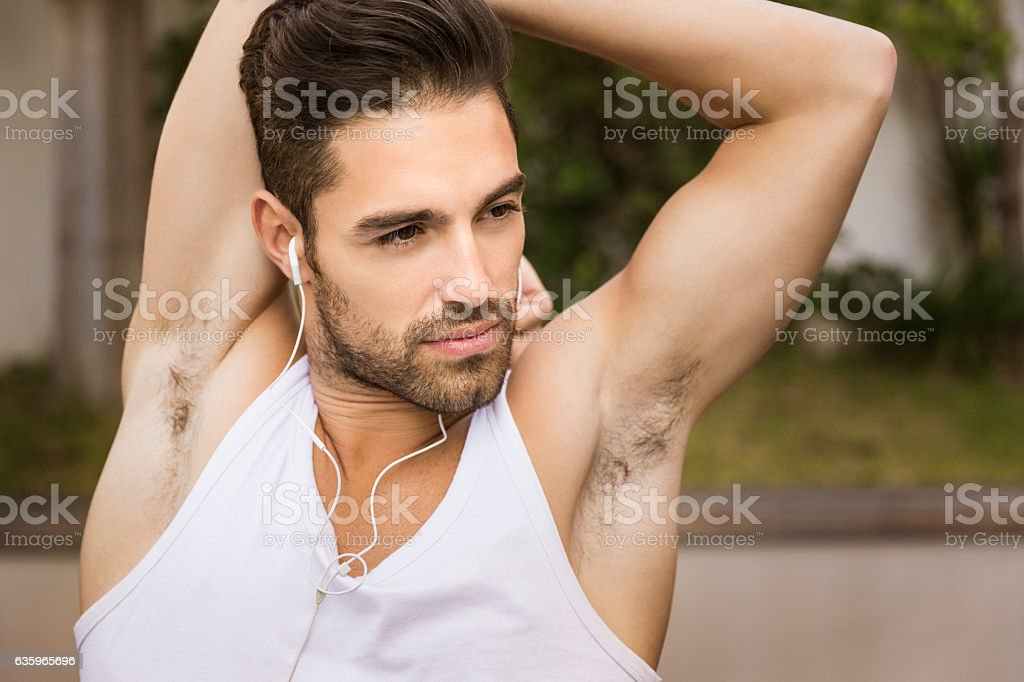 Sporty young man doing arm stretch in backyard stock photo