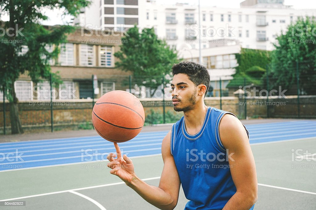 Sporty Young Man Spinning Basketball On Finger stock photo