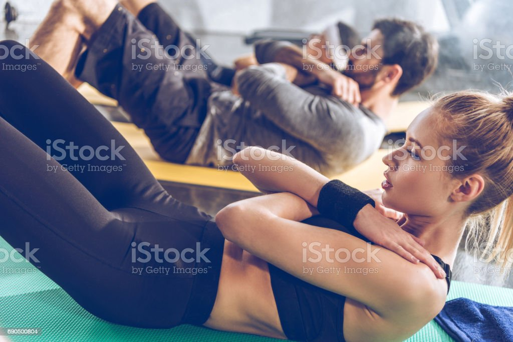 Sporty young people doing abs on yoga mats while exercising at the gym stock photo