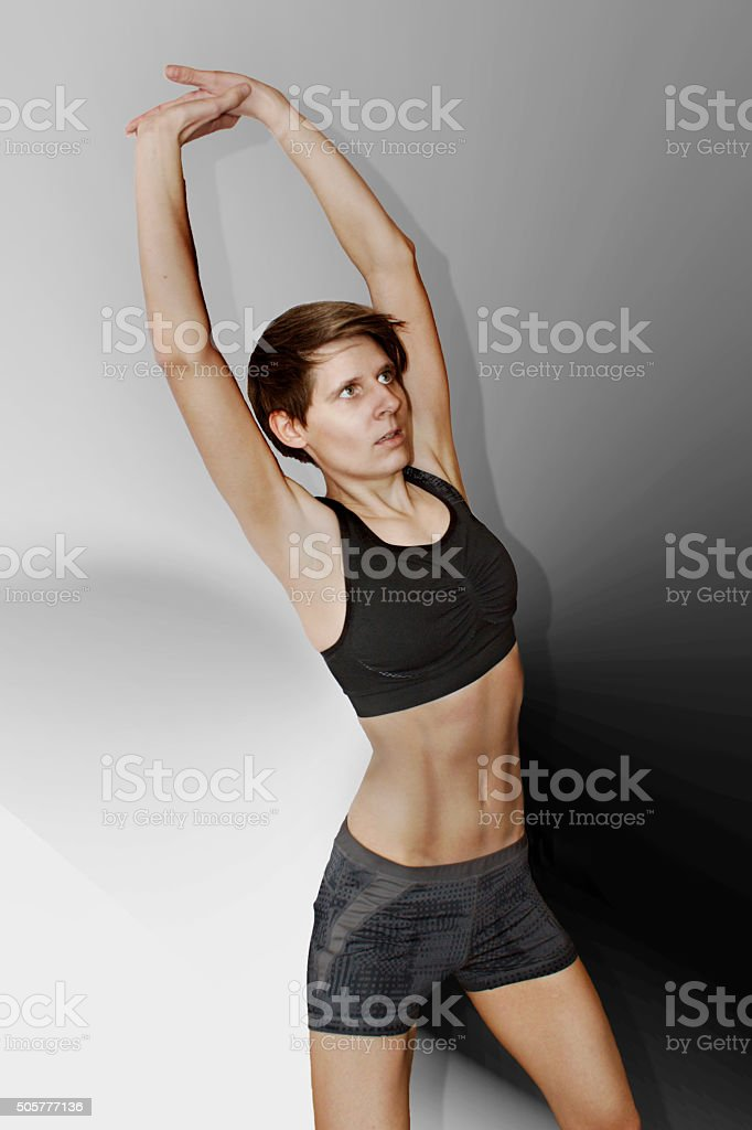 Sporty young woman against a plain background stock photo
