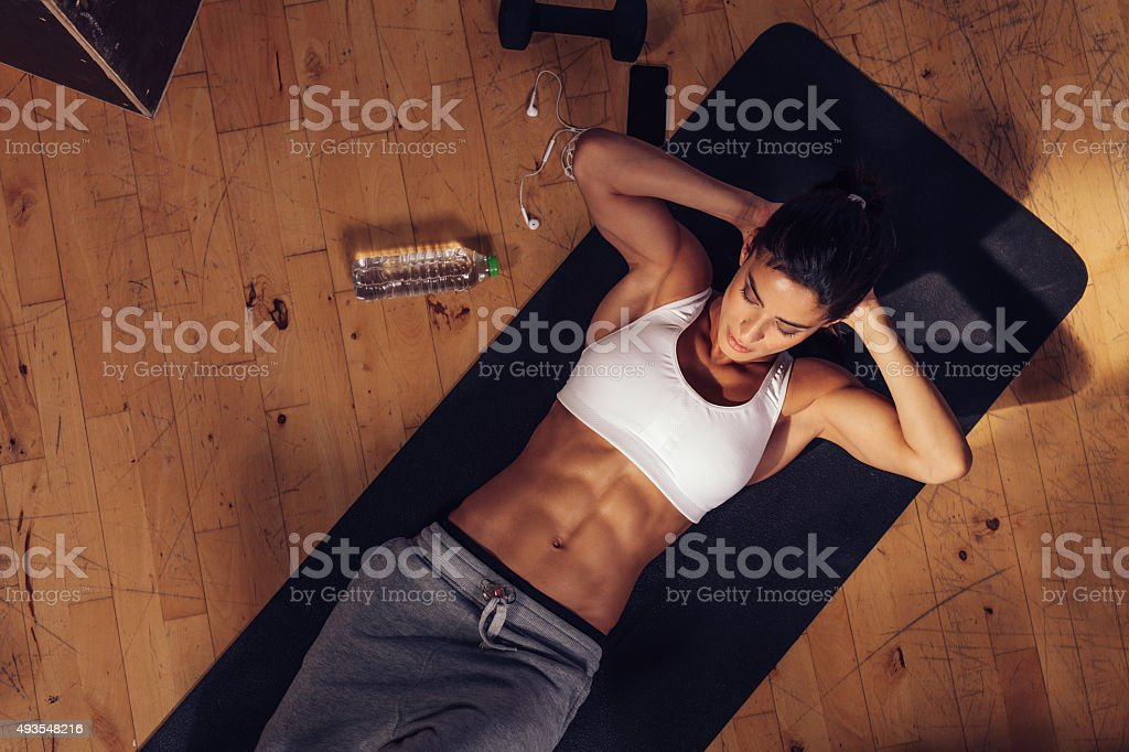 Sporty young woman doing sits-up at gym stock photo