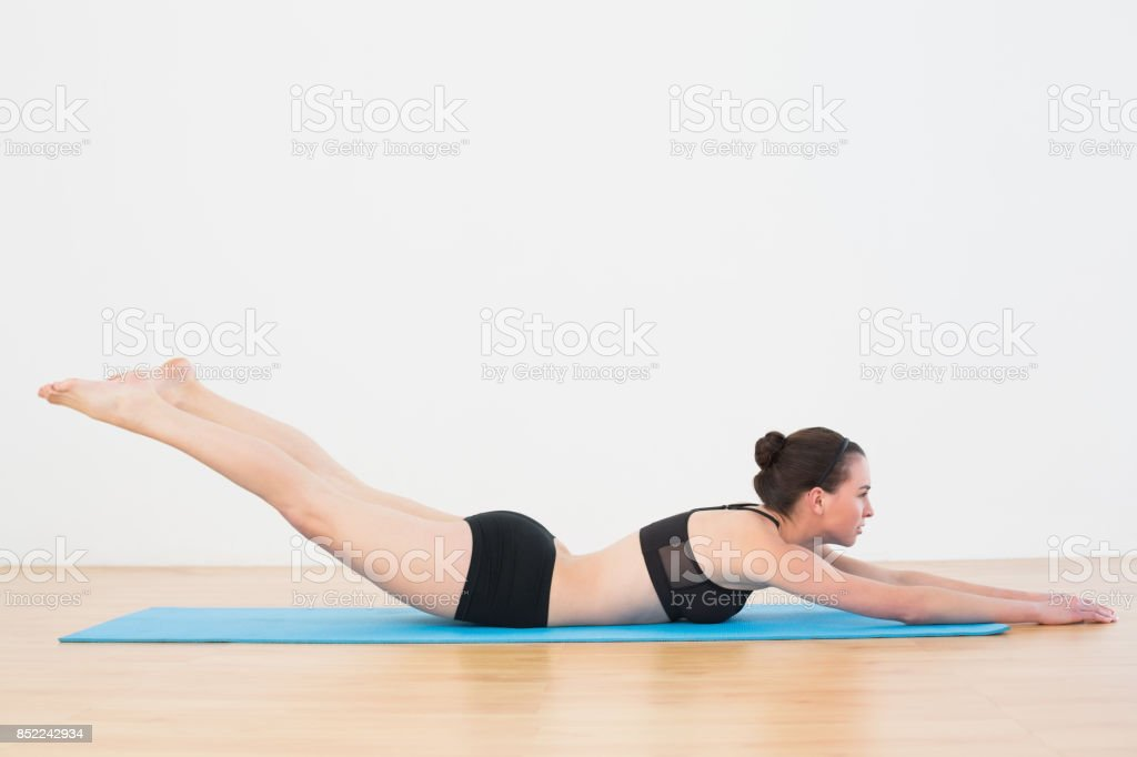 Sporty young woman doing the Locust Posture stock photo