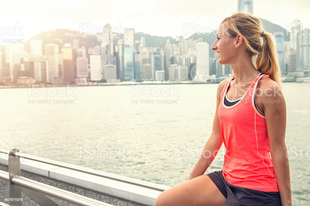 Sporty young woman in Hong Kong relaxing after training outdoors stock photo