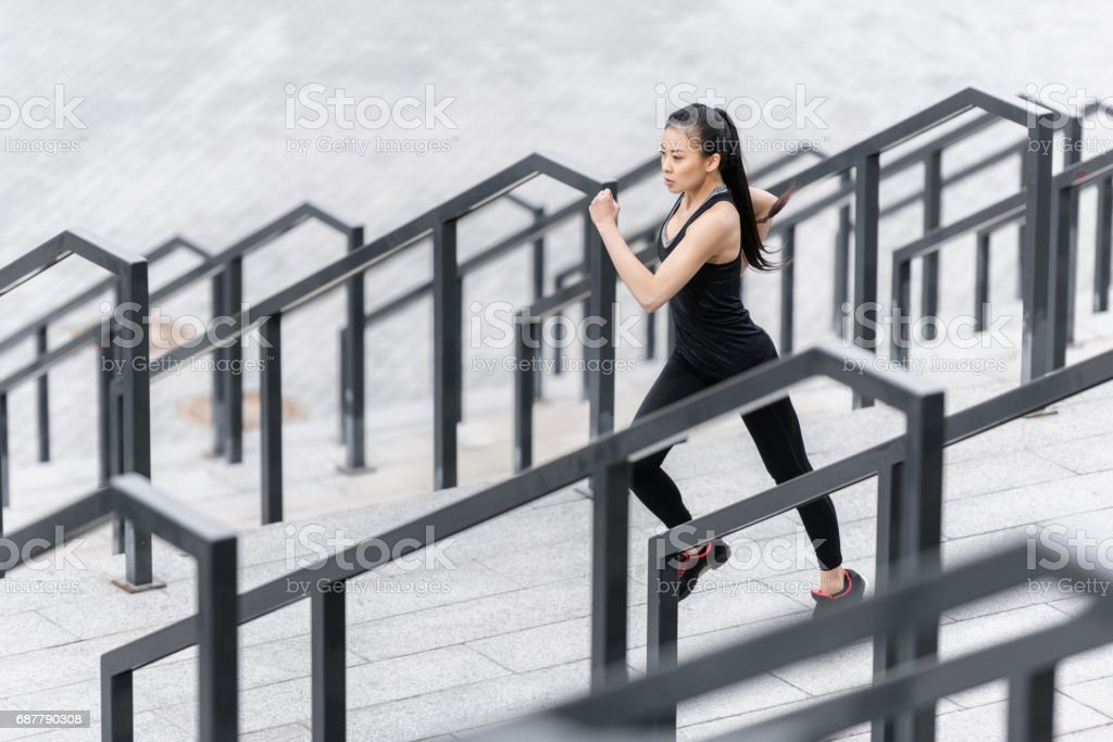 Sporty young woman in sportswear jogging on stadium stairs stock photo