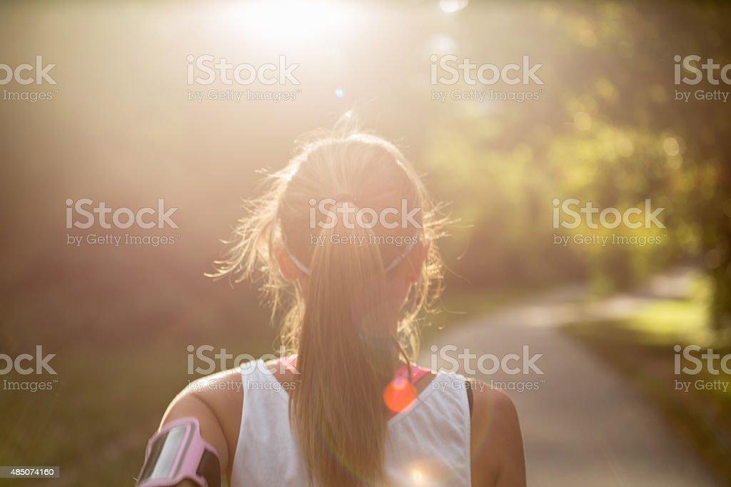 Sportliche junge Frau, die Musik hören, während du im Freien – Sonnenuntergang – Foto